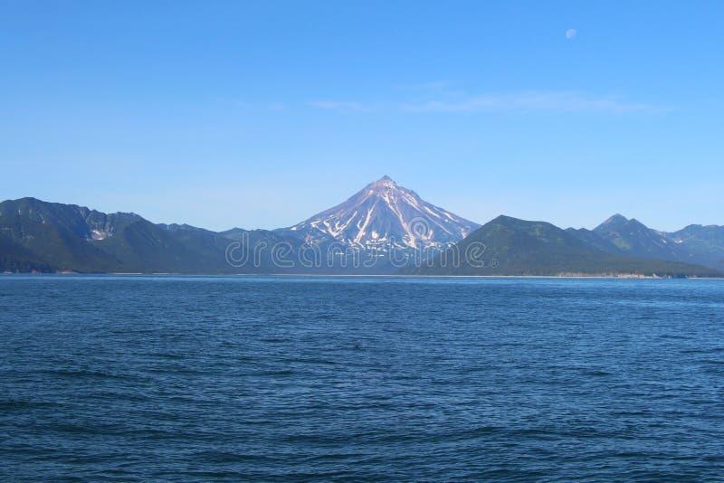 Взгляд вулкана Vilyuchinsky & x28; также вызвал Vilyuchik& x29; от воды Луна видима в небе стоковые изображения rf