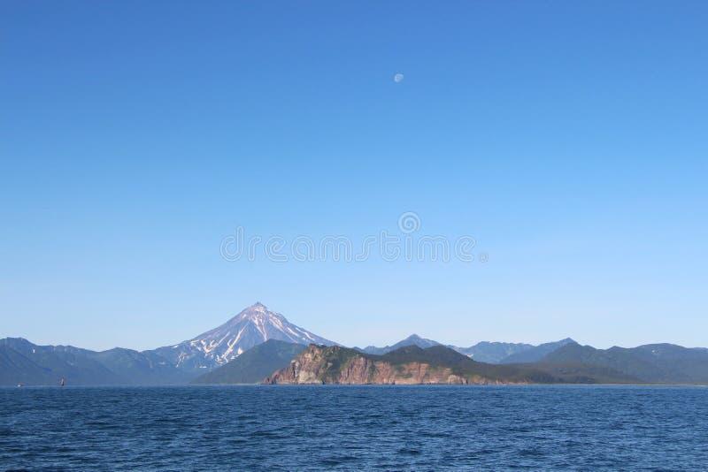 Взгляд вулкана Vilyuchinsky & x28; также вызвал Vilyuchik& x29; от воды Луна видима в небе стоковое фото