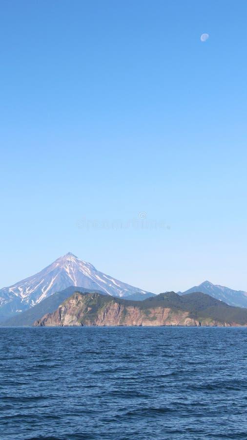 Взгляд вулкана Vilyuchinsky & x28; также вызвал Vilyuchik& x29; от воды Луна видима в небе стоковые изображения