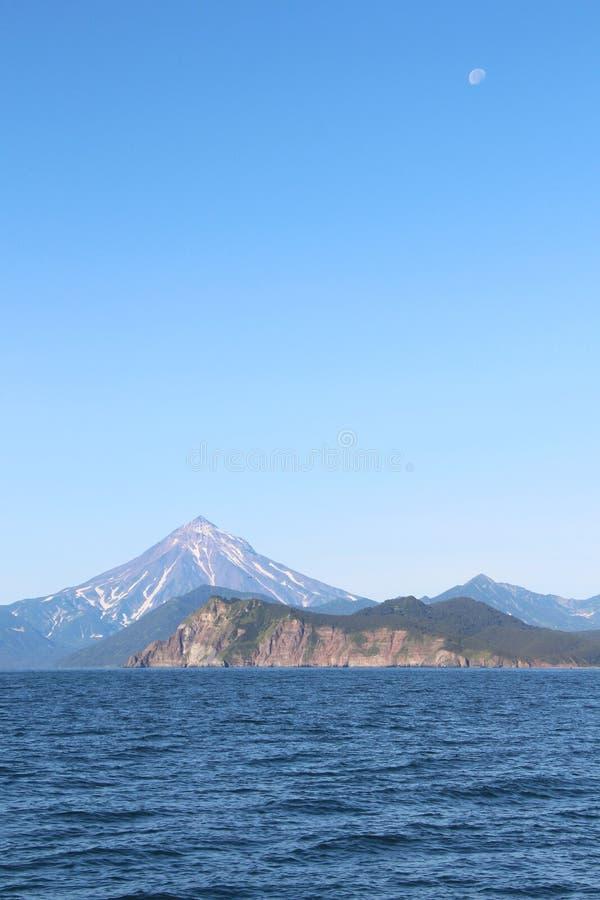 Взгляд вулкана Vilyuchinsky & x28; также вызвал Vilyuchik& x29; от воды Луна видима в небе стоковая фотография rf