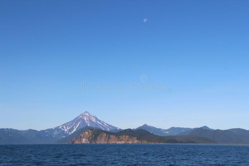 Взгляд вулкана Vilyuchinsky & x28; также вызвал Vilyuchik& x29; от воды Луна видима в небе стоковая фотография