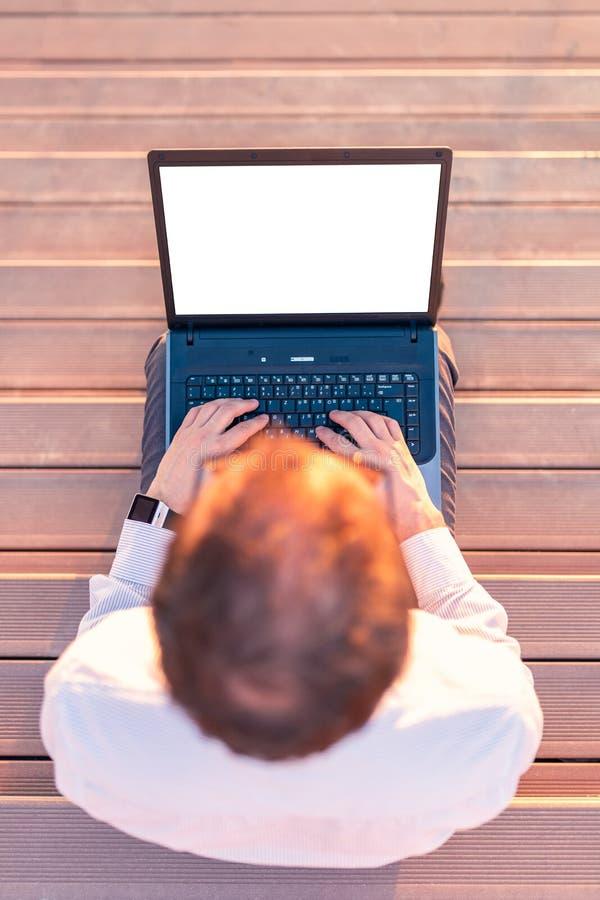 Взгляд высокого угла бизнесмена сидя на лестницах и используя ноутбук пустого экрана outdoors стоковая фотография