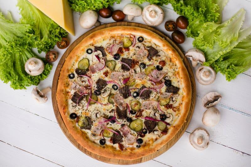 Взгляд высокого угла вкусной пиццы на таблице окруженной овощами, грибами и сыром стоковые изображения