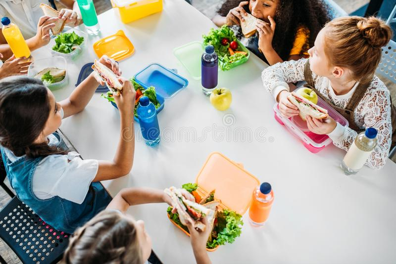 взгляд высокого угла группы в составе школьницы принимая обед на школьный кафетерий стоковая фотография
