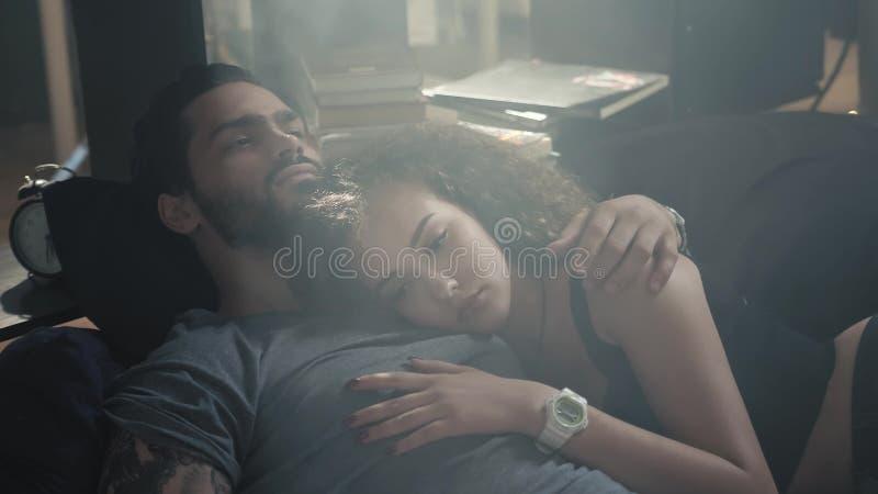 Взгляд высокого угла красивых счастливых молодых пар обнимая пока спящ на кровати, рано утром, relashionships, человек с стоковая фотография