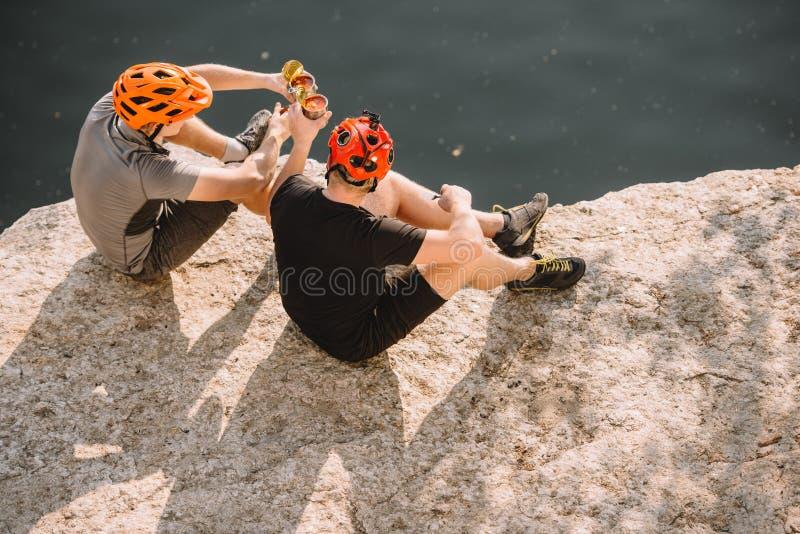 взгляд высокого угла мужских путешественников в защитных шлемах clinking консервными банками на скалистой скале стоковые фото