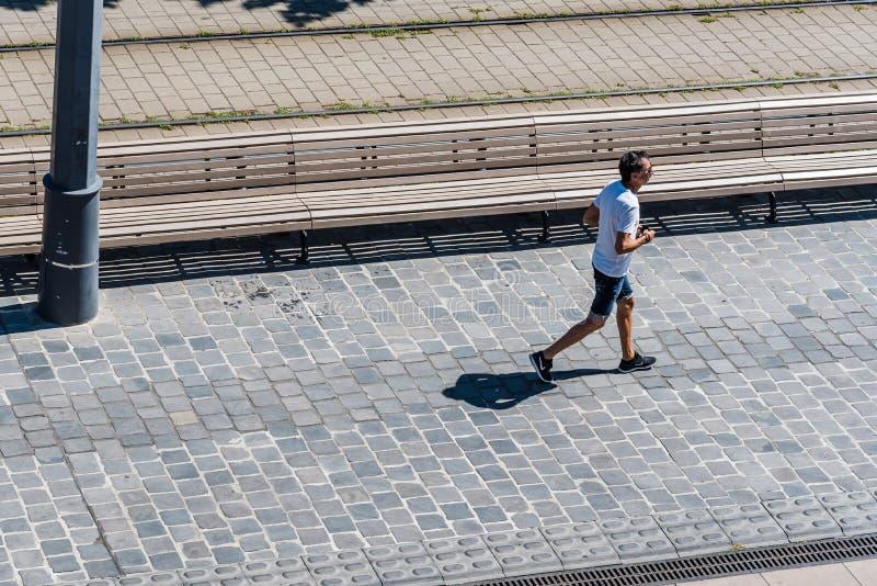 Взгляд высокого угла неопознанного мужского бегуна jogging на дороге стоковые изображения rf