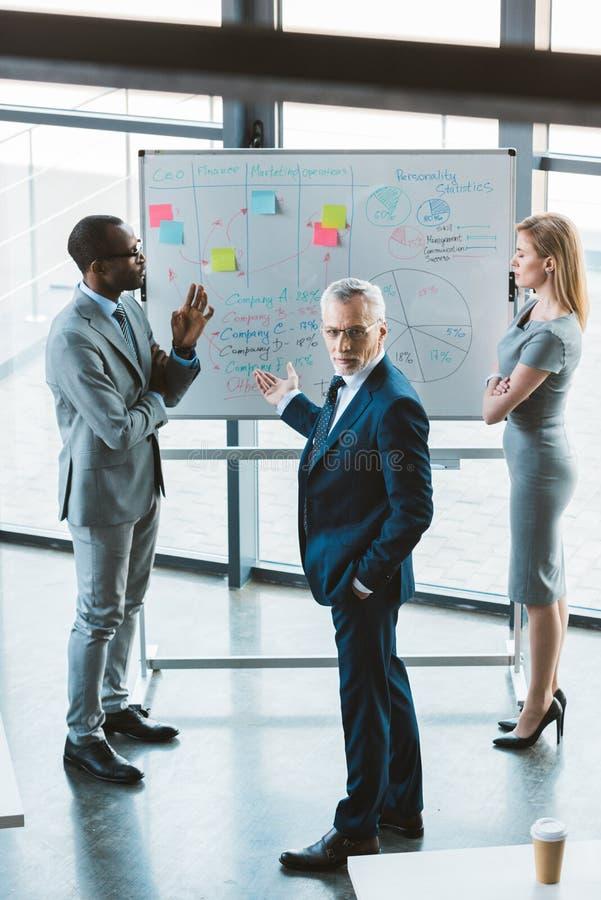 взгляд высокого угла профессиональных многонациональных бизнесменов обсуждая диаграммы и диаграммы стоковые изображения rf