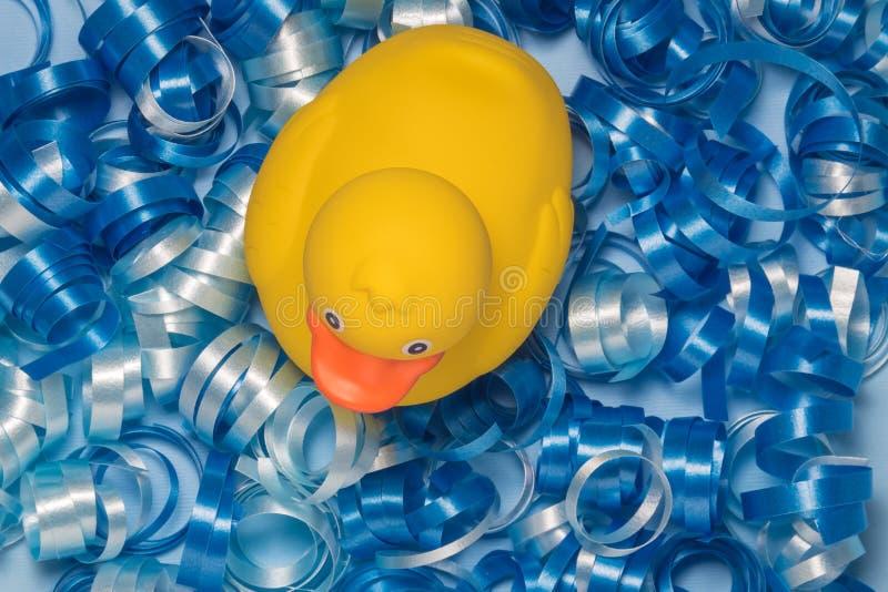 Взгляд высокого угла резиновой утки на голубой декоративной ленте соединяет стоковые изображения rf