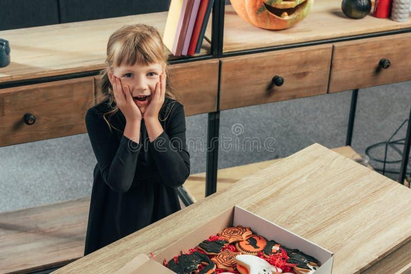 взгляд высокого угла сотрясенного ребенк смотря камеру на столешнице с печеньями хеллоуина в коробке стоковая фотография rf