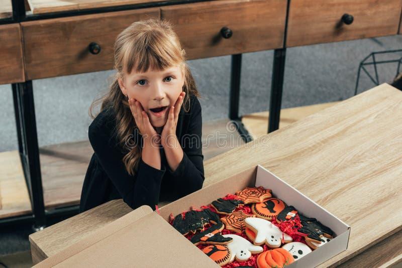 взгляд высокого угла сотрясенного ребенк смотря камеру на столешнице с печеньями хеллоуина в коробке стоковые изображения