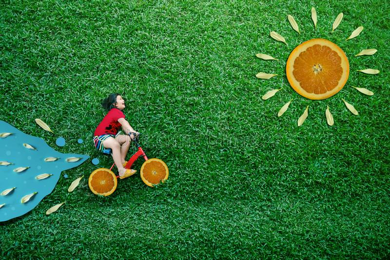 Взгляд высокого угла счастливые азиатские дети Девушка на велосипеде кладет вниз на зеленую лужайку во дне лета солнечном Воображ стоковая фотография