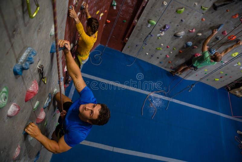 Взгляд высокого угла уверенно спортсменов взбираясь стена в клубе стоковое фото