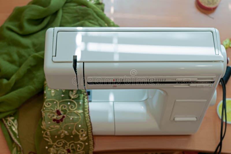Взгляд высокого угла швейной машины с зеленой тканью на деревянном столе в студии стоковая фотография rf