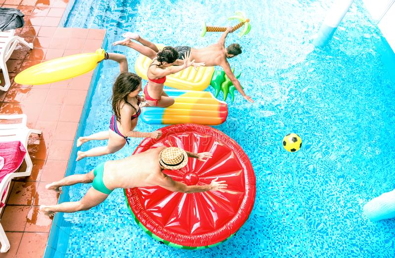 Взгляд высокого угла millenial друзей скача на партию бассейна - концепцию каникул молодости со счастливыми парнями и девушками и стоковая фотография rf
