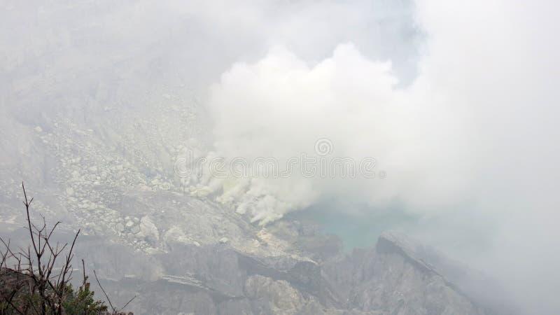 Взгляд в кратер активного вулкана Kawah Ijen где кисловочное озеро обнаруж стоковое изображение