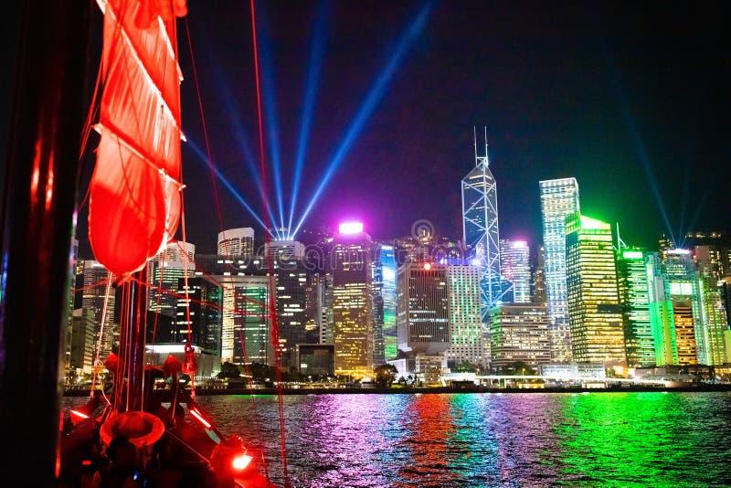 Взгляд гавани Гонконга от традиционной шлюпки старья вечером во время известного шоу лазера Перемещение в Китае, Азии Плавание на стоковое изображение rf