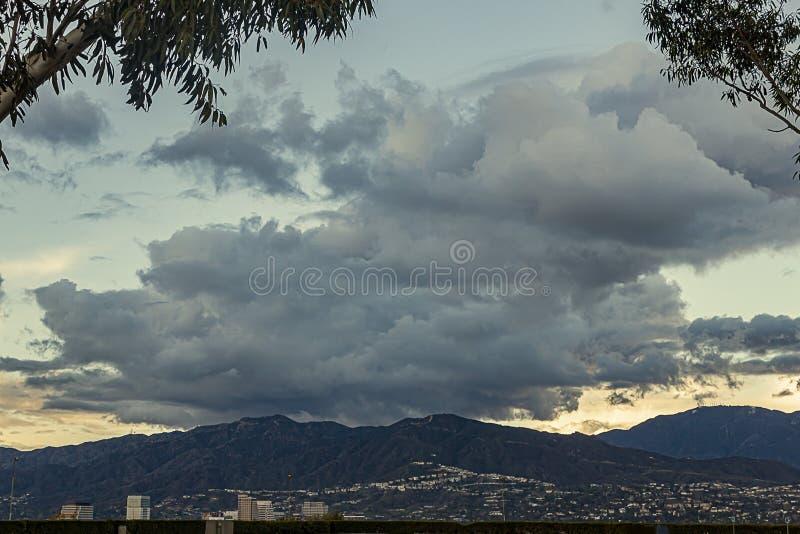 Взгляд горного склона домов с горами садов и большими облаками с башнями дела glendale стоковые изображения rf