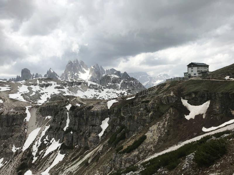Взгляд горных пиков и утесов доломитов в Италии в Auronzo di Cadore в Тироле Здание гостиницы под overcast стоковые фотографии rf