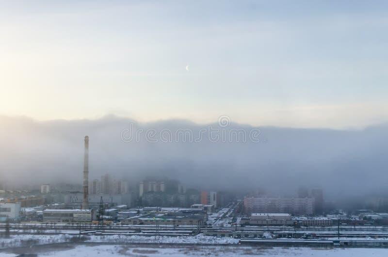 Взгляд города положенного в кожух в смог утра, в небе луна стоковые изображения