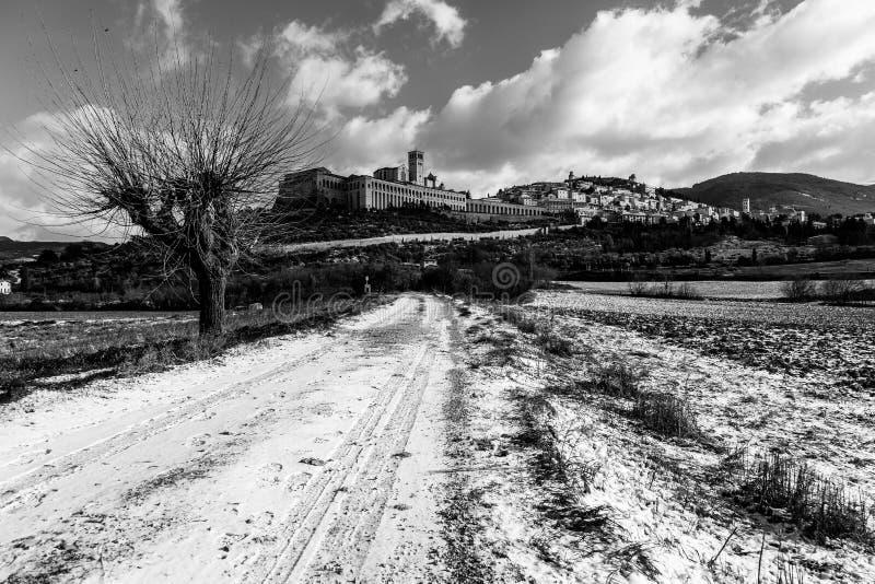 Взгляд городка Умбрии Assisi в зиме, при проселочная дорога покрытая снегом и небом с белыми облаками стоковая фотография