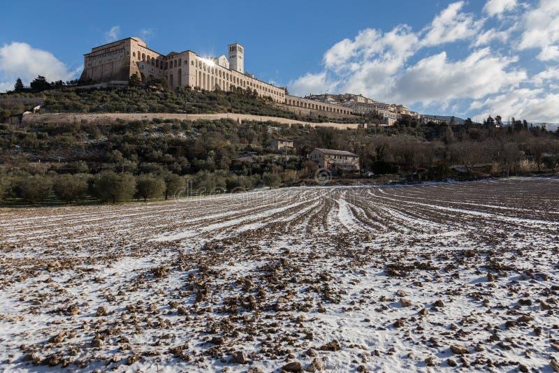 Взгляд городка Умбрии Assisi в зиме, с полем покрытым снегом и голубым небом с белыми облаками стоковое фото rf