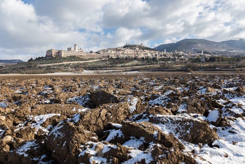 Взгляд городка Умбрии Assisi в зиме, с полем покрытым снегом и голубым небом с белыми облаками стоковое изображение
