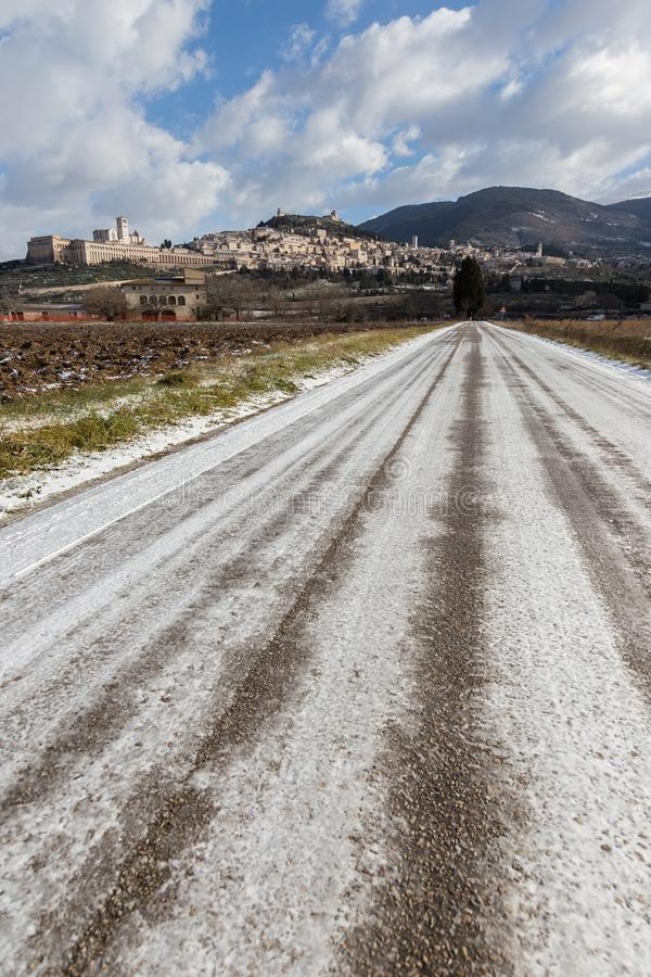 Взгляд городка Умбрии Assisi в зиме, с проселочной дорогой покрытой снегом и голубым небом с белыми облаками стоковые изображения rf