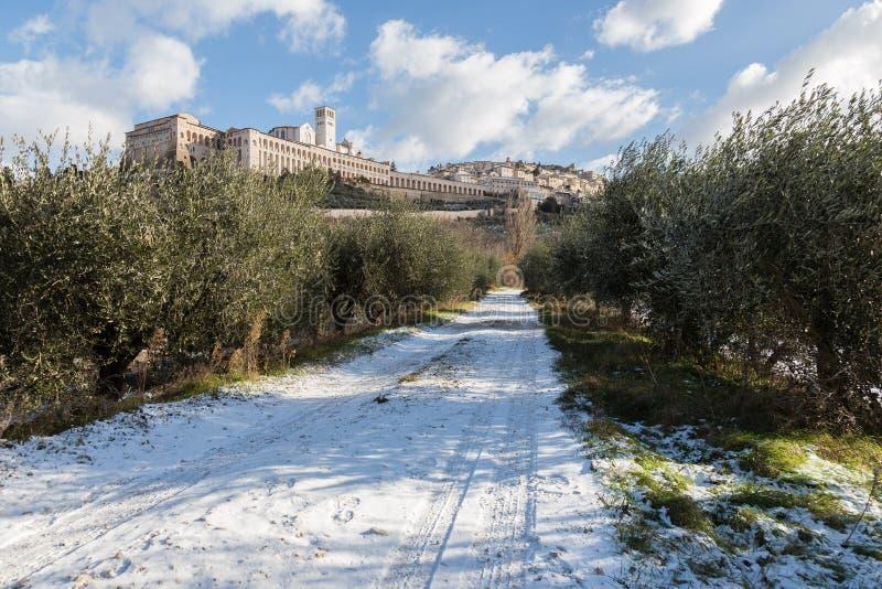 Взгляд городка Умбрии Assisi в зиме, с проселочной дорогой покрытой снегом и голубым небом с белыми облаками стоковое фото