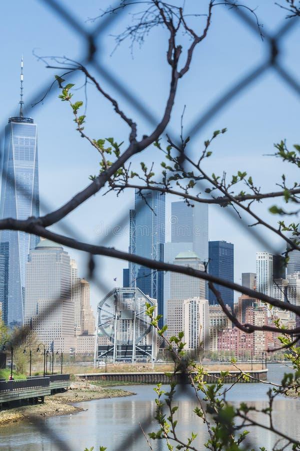 Взгляд городского пейзажа Нью-Йорка, более низкого Манхаттана от Jersey City через решетку стоковая фотография