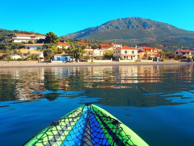 Взгляд греческой горы и рыбацкого поселка отраженных в воде Gulf of Corinth стоковое фото