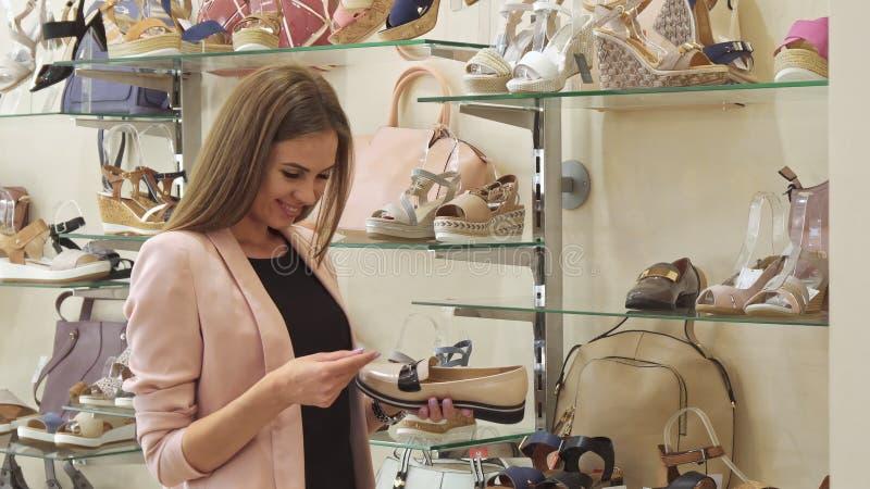 Взгляд девушки на цене ботинок на магазине стоковые фото