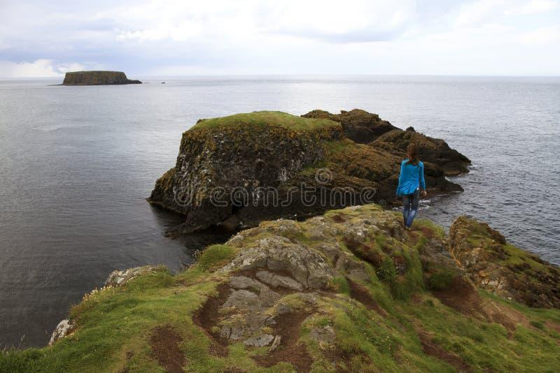 Взгляд девушки прибрежный пейзаж около Carrick Rede стоковое изображение