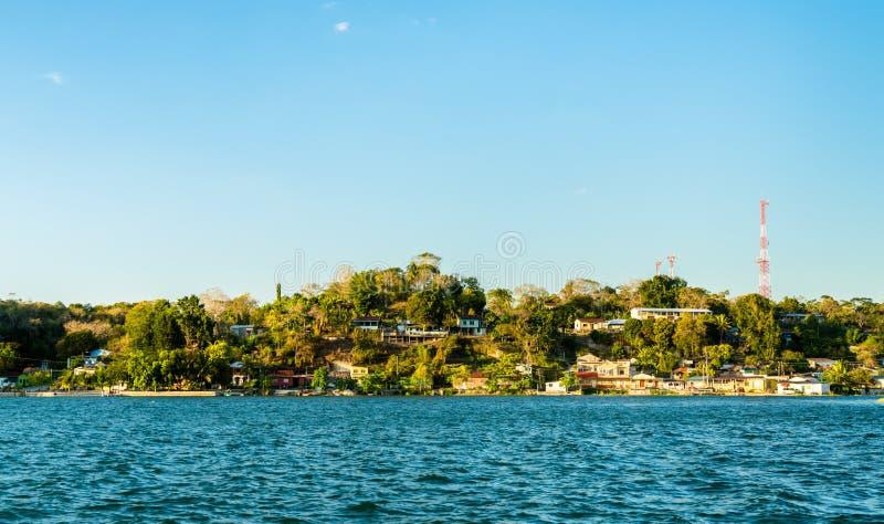 Взгляд деревни San Miguel через озеро Peten Itza, Гватемалу стоковые изображения