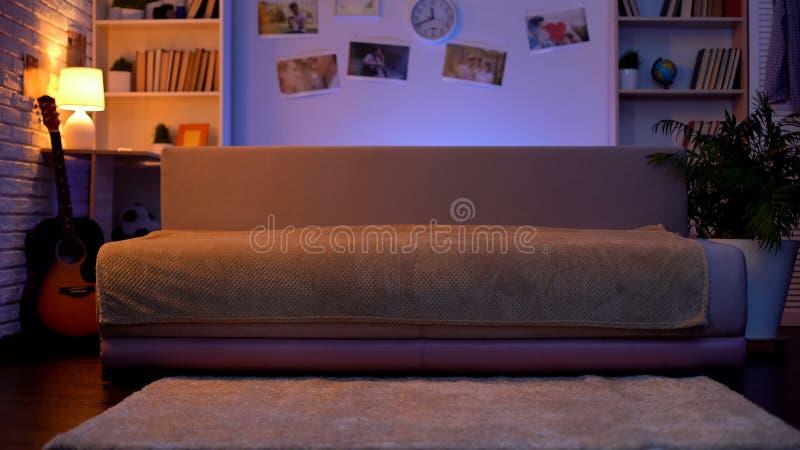 Взгляд для того чтобы опорожнить комнату подростка, положение софы на середине и гитару на своей стороне стоковая фотография
