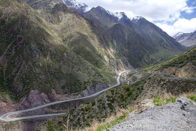 Взгляд дороги горы между зелеными холмами и снег-покрытыми пиками горных цепей и облачным небом стоковое изображение