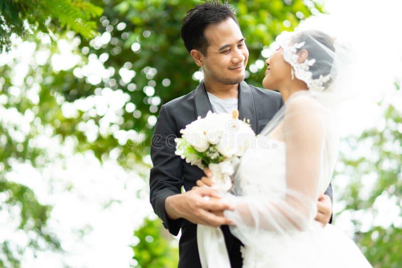 Взгляд жениха и невеста на одине другого при влюбленность держа bokeh стоковое изображение rf