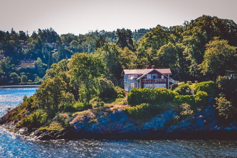 Взгляд жилого дома, стоя на холме острова леса с каменным берегом на солнечный яркий день, Швеция стоковая фотография