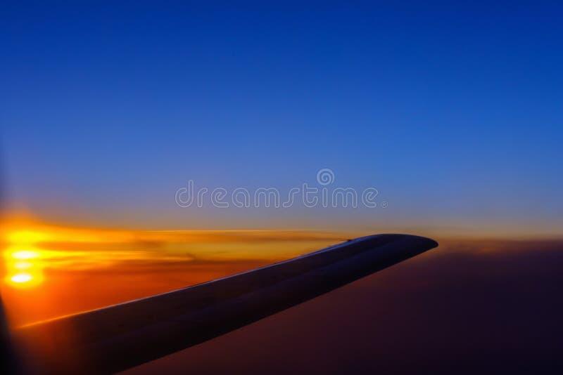 Взгляд захода солнца и крыла воздушных судн от иллюминатора стоковое изображение