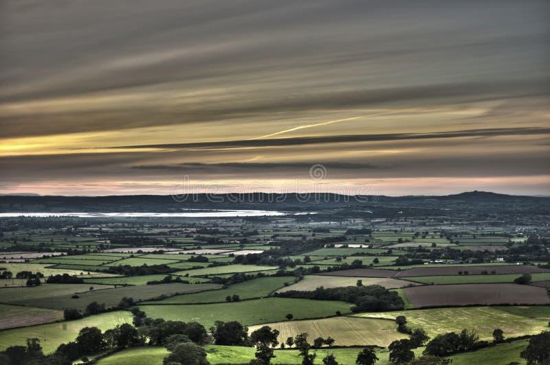 Взгляд захода солнца над сочный аграрным краем стоковые фотографии rf
