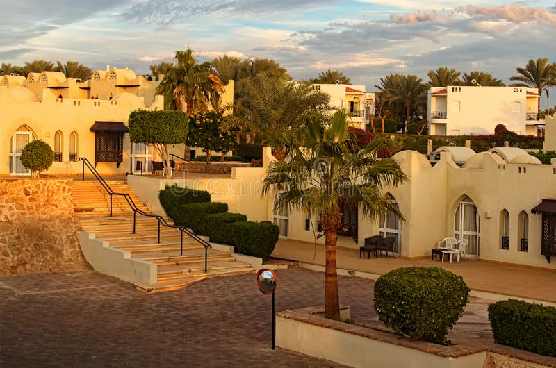 Взгляд здания гостиницы курорта с пальмами и кустами во время захода солнца шейх sharm Египета el Принципиальная схема каникулы л стоковое изображение rf