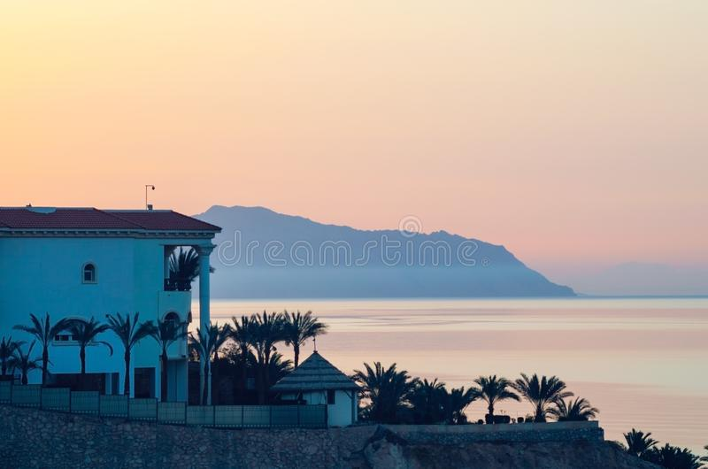 Взгляд здания гостиницы, моря и гор на восходе солнца, рассвете на курорте в Египте стоковое фото