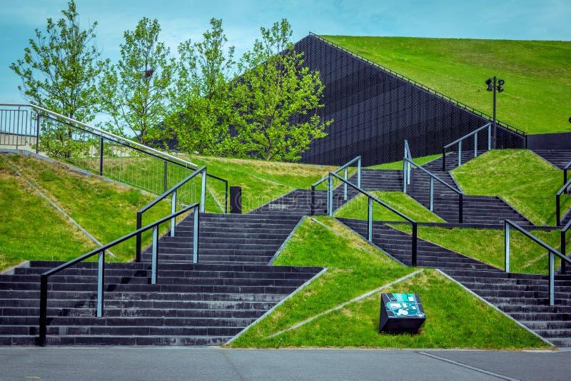 Взгляд зеленых лужаек и черные лестницы приближают к международному конгрессу Hall в Катовице стоковое изображение