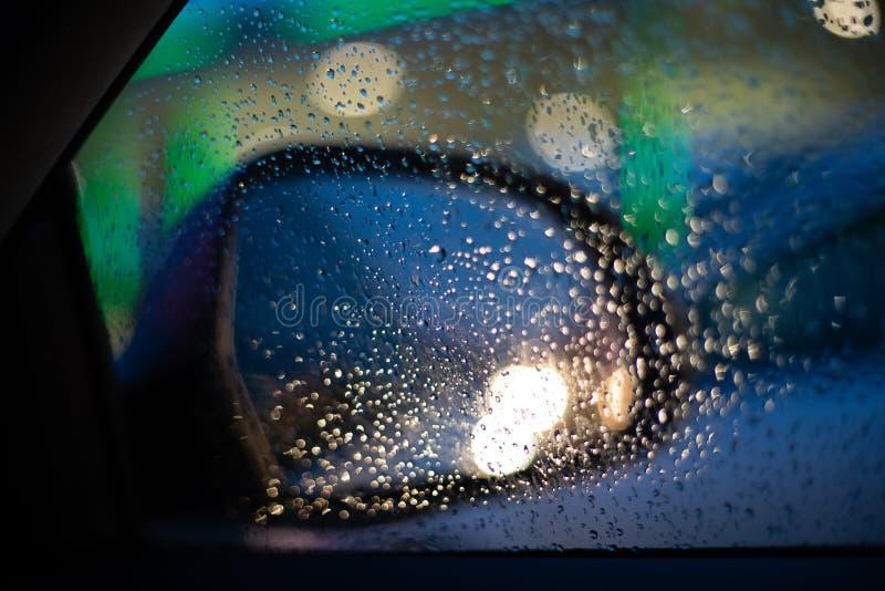 Взгляд зеркала автомобиля правый задний изнутри автомобиля с падениями на окне стоковые изображения rf
