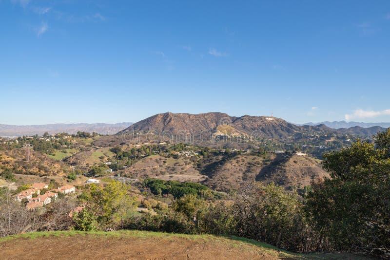 Взгляд знака Голливуд от Hollywood Hills кот день наблюдает сидит солнечный вал теплый Красивые облака в голубом небе стоковые фотографии rf