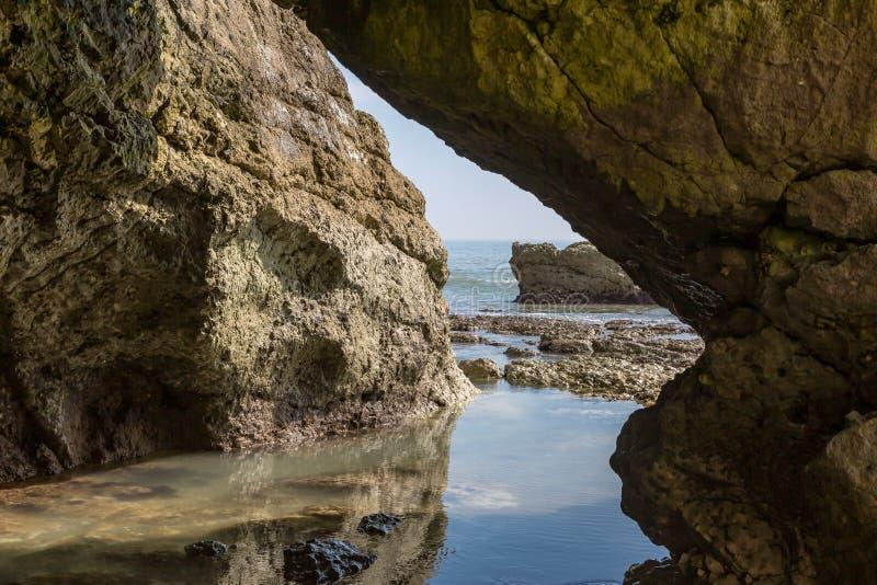 Взгляд изнутри пещеры на пляже стоковое фото rf