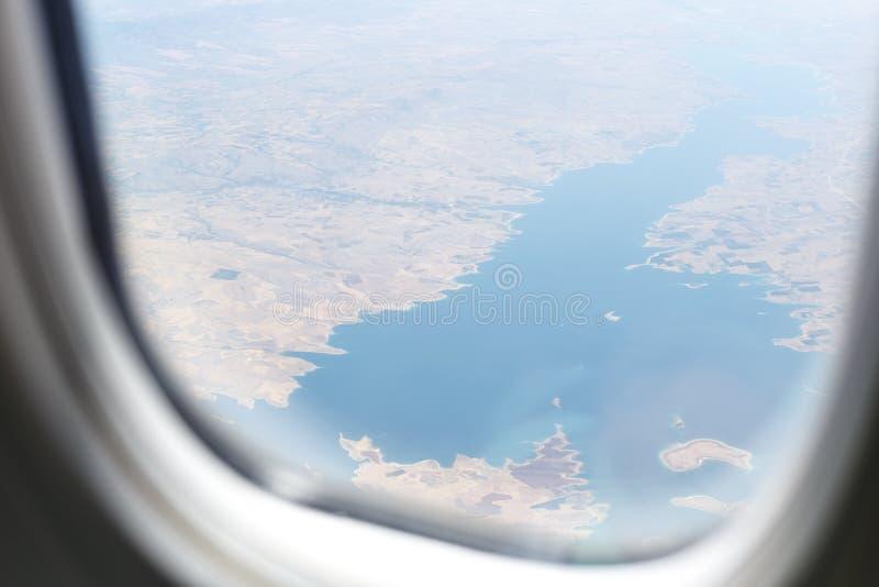 Взгляд из окна воздушных судн на ландшафтах ниже, горы, озера, леса, моря Окно воздушных судн стоковые изображения rf