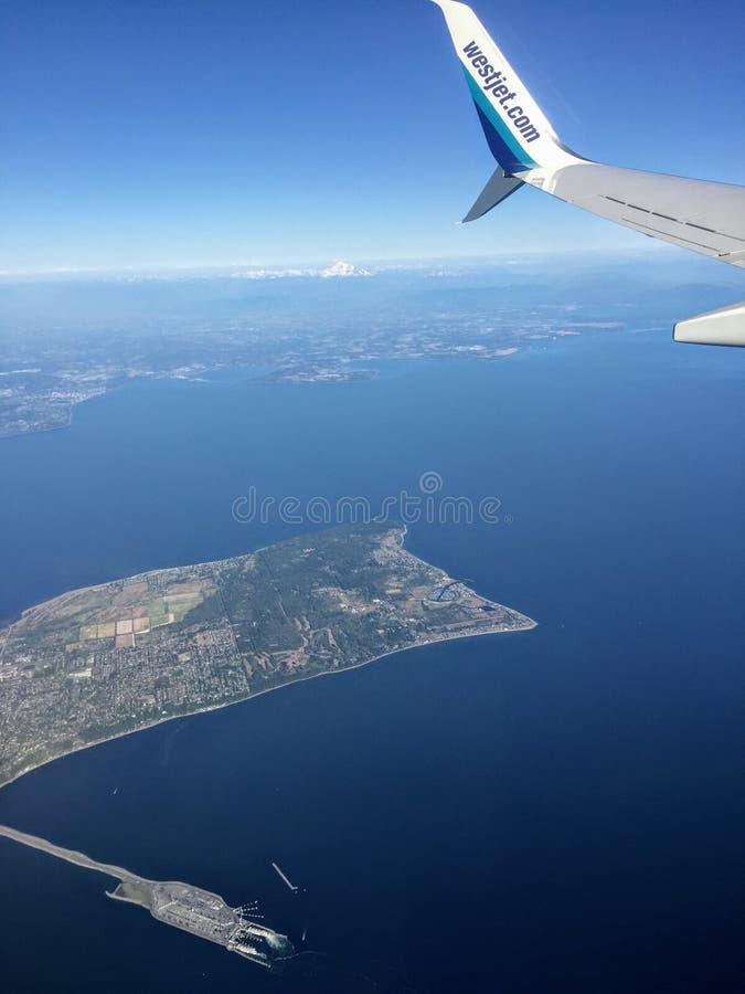 Взгляд из окна пассажира крыла летания самолета Westjet над океаном Виктория, Британской Колумбии, Канады стоковая фотография rf