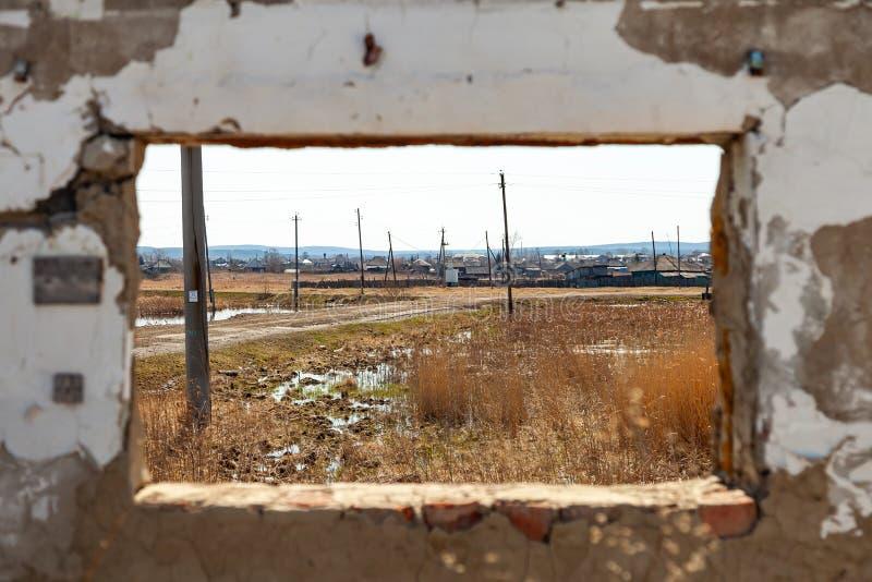 Взгляд из старого загубленного окна здания на топи с сериями старых штендеров и полу-покинутой деревне на стоковые изображения