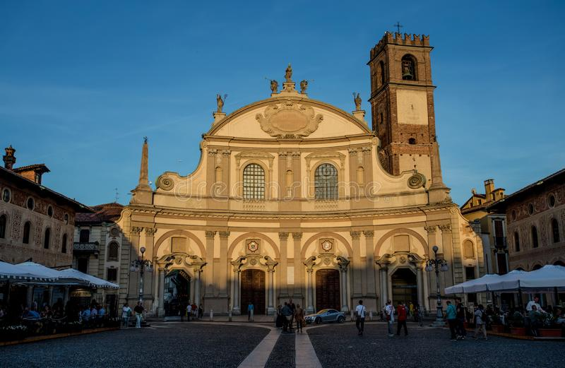 Взгляд квадрата Дукале с церковью Ambrogio в Vigevano на заходе солнца, провинции Павии, Италии стоковое изображение